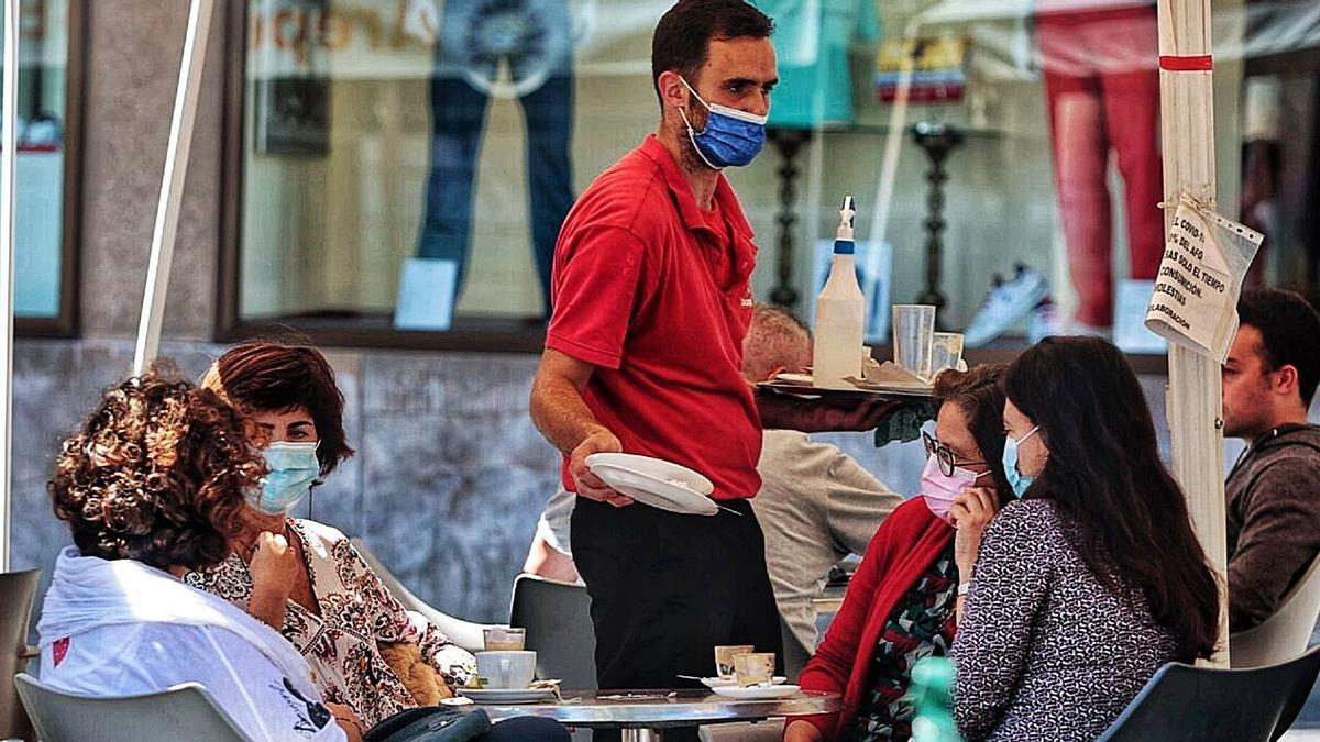 Un camarero atiende a varias clientas en una terraza del centro de Santa Cruz de Tenerife .