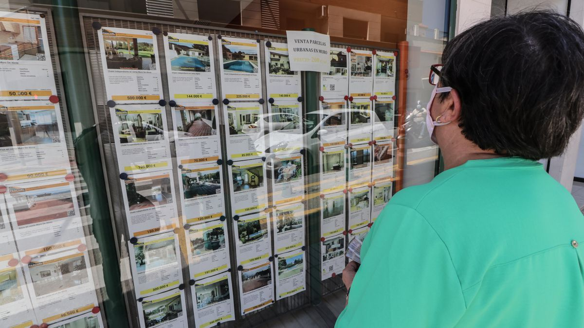 A woman looks at the window of a real estate agency.