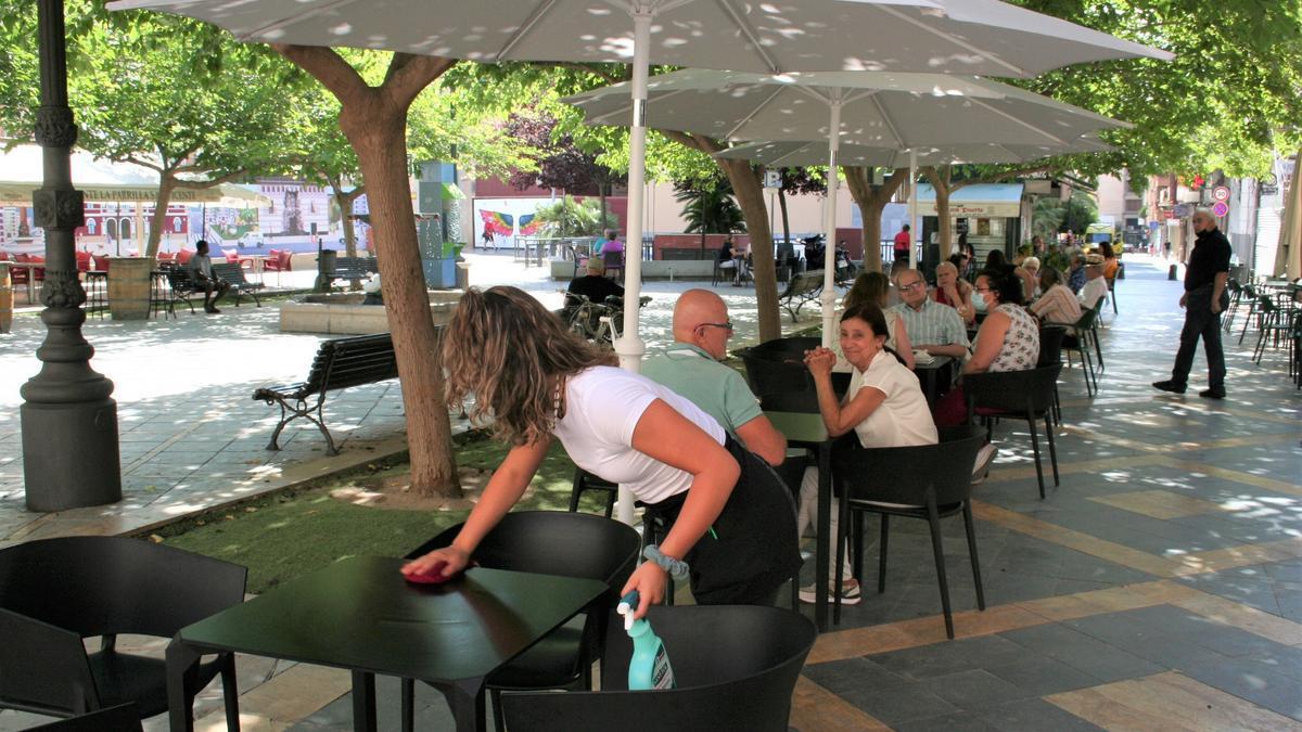 Una camarera limpia una mesa en una terraza de San Vicente.