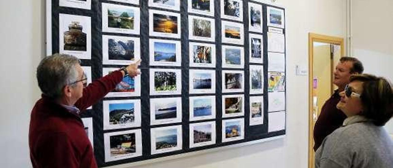Miembros de Asearpo comentan las fotos realizadas por los socios y que están expuestas en el Multiusos de Chapela. // Marta G. Brea