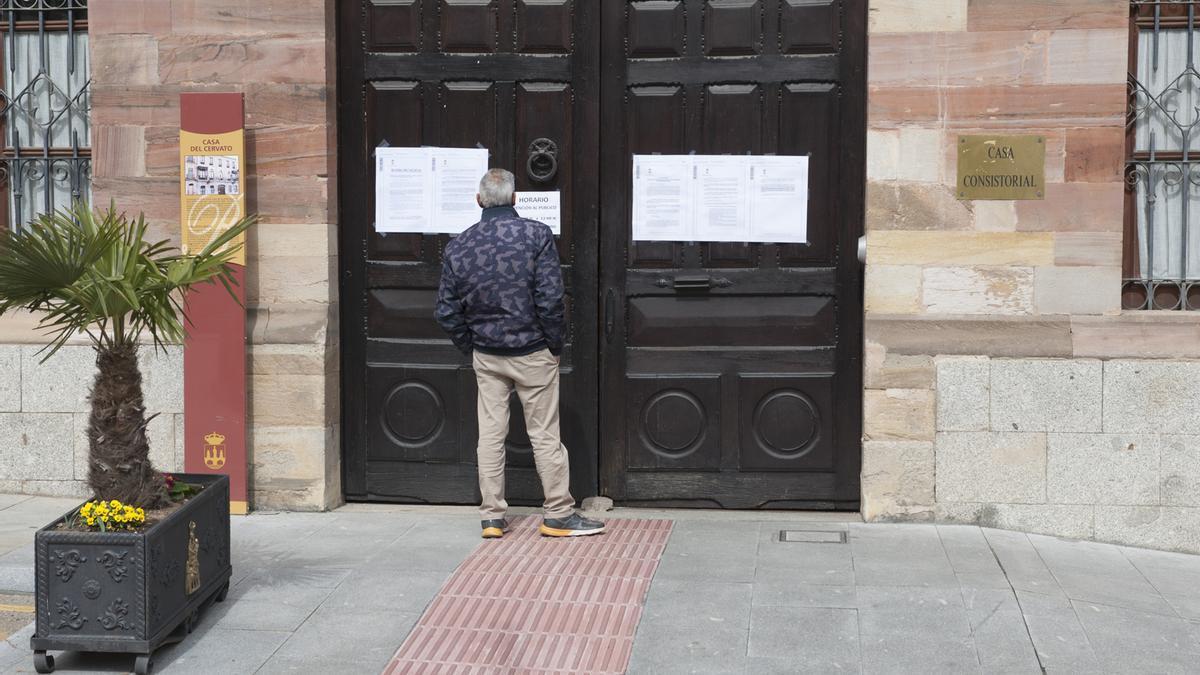 Un hombre lee los bandos municipales en las puertas del Consistorio de la plaza del Grano durante la pandemia.