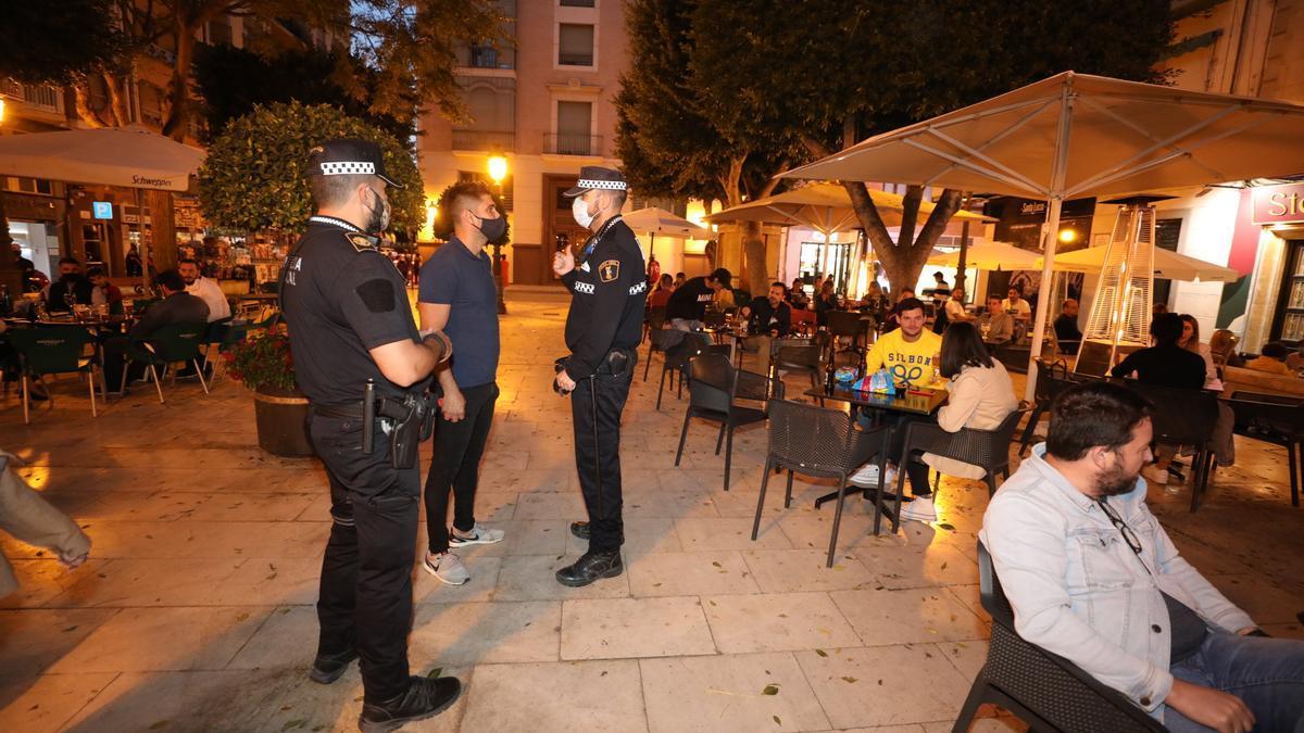 Policías de Alicante, este pasado fin de semana, en una zona de ocio. A la derecha, la Policía informa a locales de ocio de las nuevas restricciones horarias en Elche, el viernes.