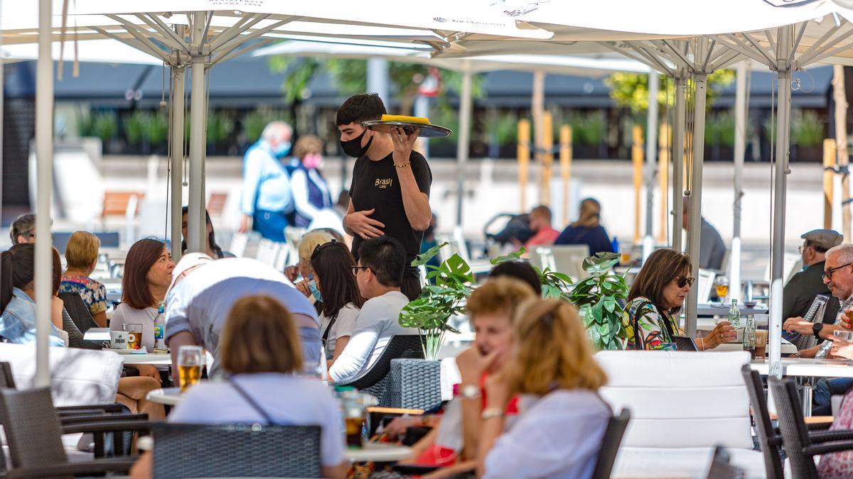 Un camarero atiende una terraza con turistas españoles en Benidorm.