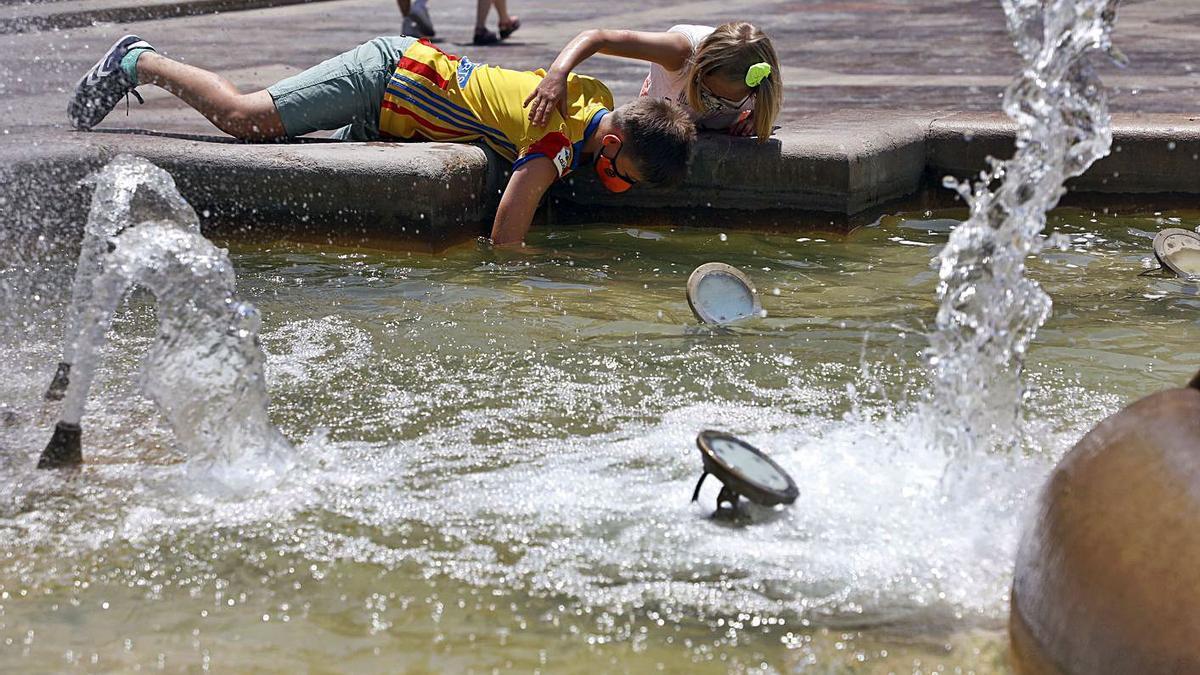 Unos niños juegan con el agua de la fuente de la plaza de la Virgen, hace unos días. | M.A.MONTESINOS