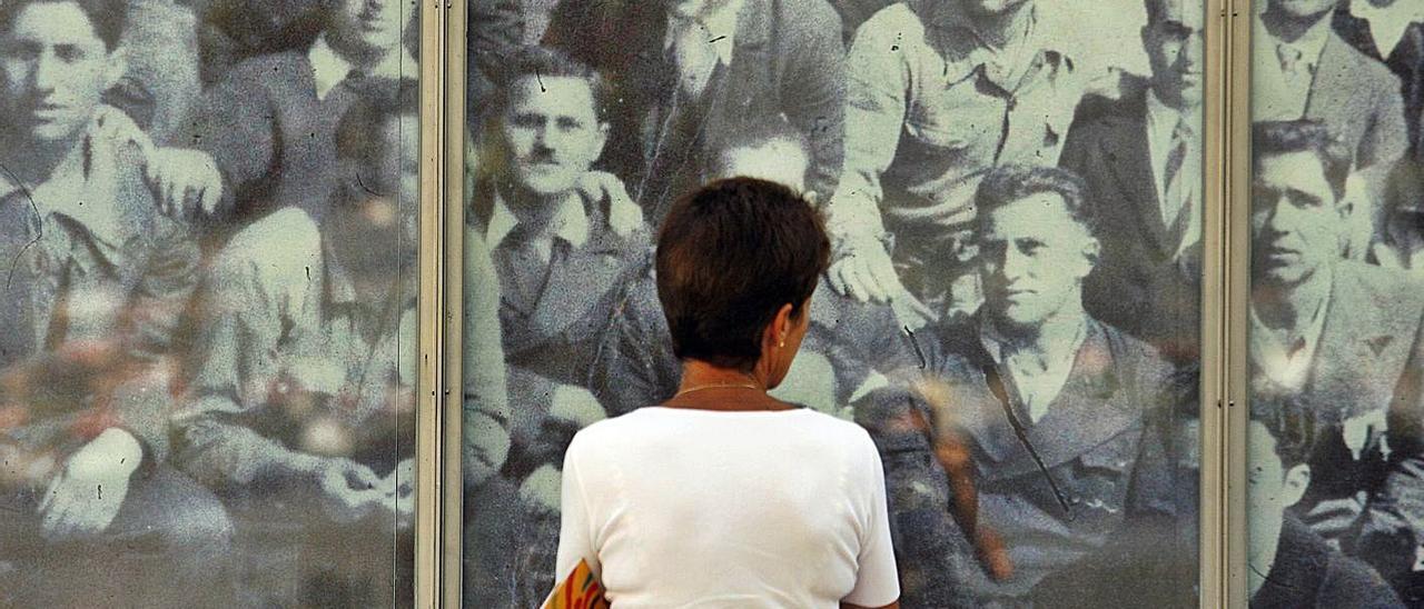 Una mujer contempla los rostros de represaliados en un acto de homenaje en la isla de San Simón.   | // R.E.