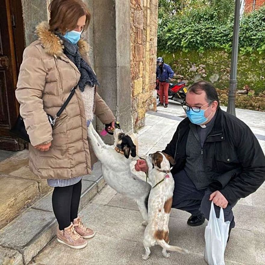 """El sacerdote David Cuenca saluda a las mascotas de Luz Padilla, """"Pepa"""" y """"Lola""""."""