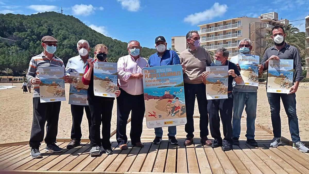 El alcalde y los vecinos, ayer, con los carteles que prohíben fumar en la playa. | ASJ