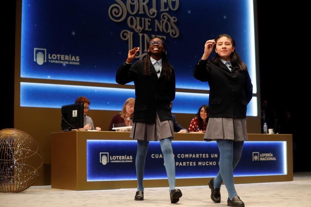 Las niñas del colegio de San ildefonso Yanisse Alexandra Soto (d) y Elisabeth Obarisiagbon Iyamu muestran las bolas con el número 74.770 que ha sido agraciado con uno de los quintos premios.