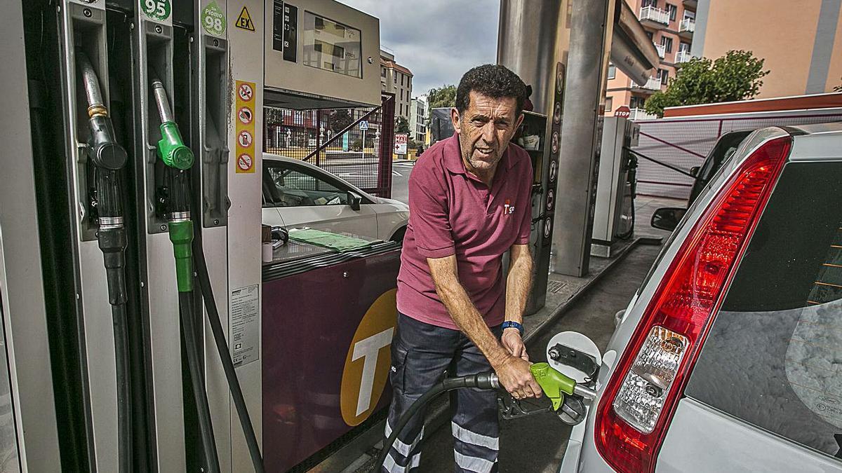 Un trabajador reposta un vehículo en una gasolinera.