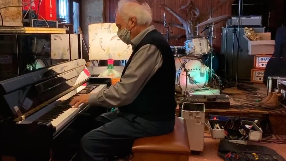 Alfonso Galbán tocando el piano de El Náutico al lado de la chimenea