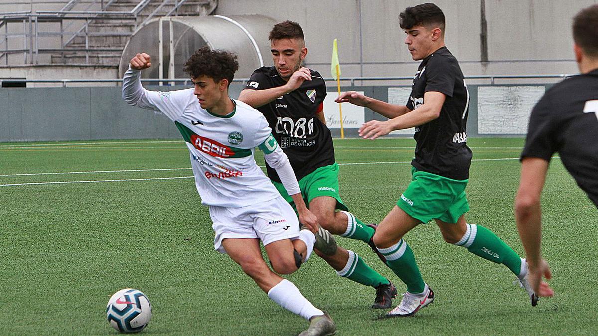 Un jugador del Pabellón intenta salir de la presión de dos rivales del Ural, ayer en el campo Miguel Ángel González. |  // IÑAKI OSORIO