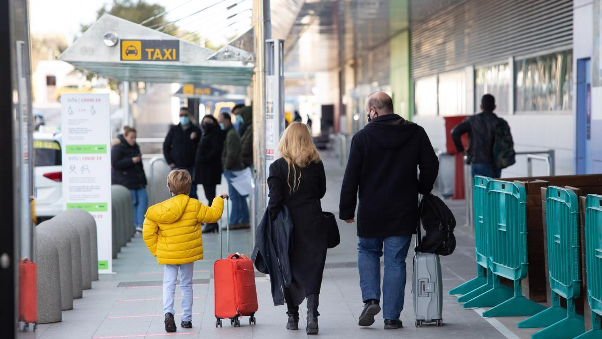 Un niño y dos adultos abandonan la terminal del aeropuerto.