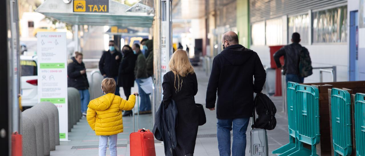 Un niño y dos adultos abandonan la terminal del aeropuerto. Vicent Marí
