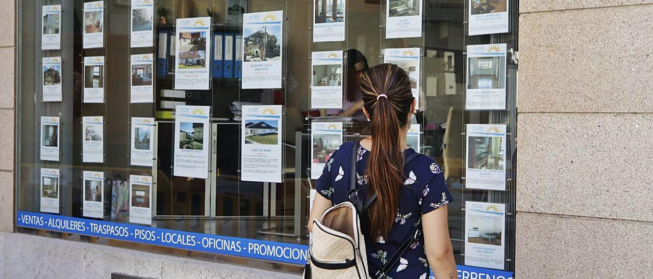Una joven mira el escaparate de una inmobiliaria.