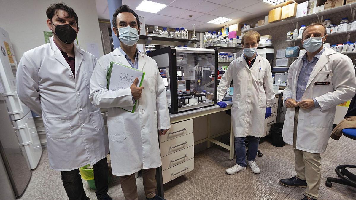 Pola esquierda, Alberto García y Francisco García Carro, de la inxeniería Magna Dea, y Javier Fernández y Felipe Lombó, de la Universidá d'Uviéu, col so prototipu de detección del covid n'agües residuales, nun llaboratoriu de la Facultá de Medicina.