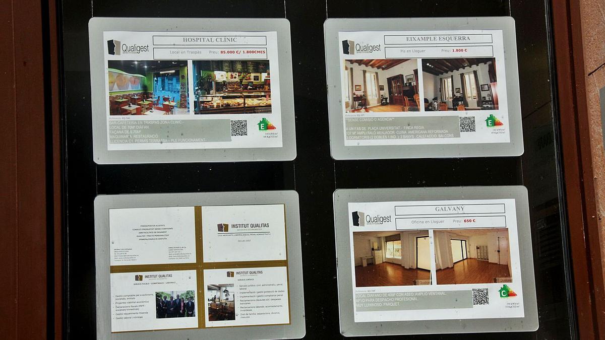 Cartells d'habitatges en una agència immobiliària. | SÍLVIA JUNYENT DALMAU