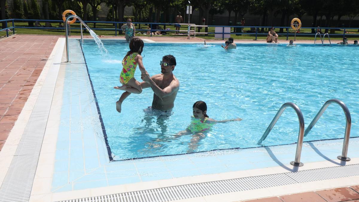 José Antonio juega con sus hijas Vera y Elena esta mañana de sábado en la piscina de La Granja, en Zaragoza.