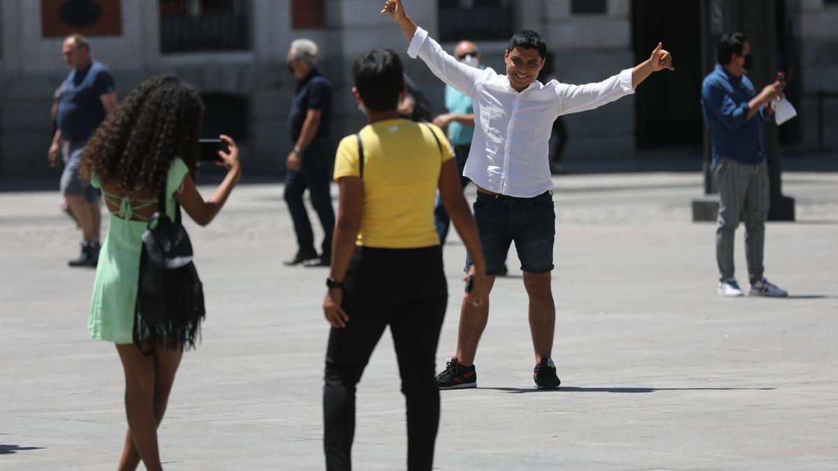 Un turista se hace una foto en la Puerta del Sol.