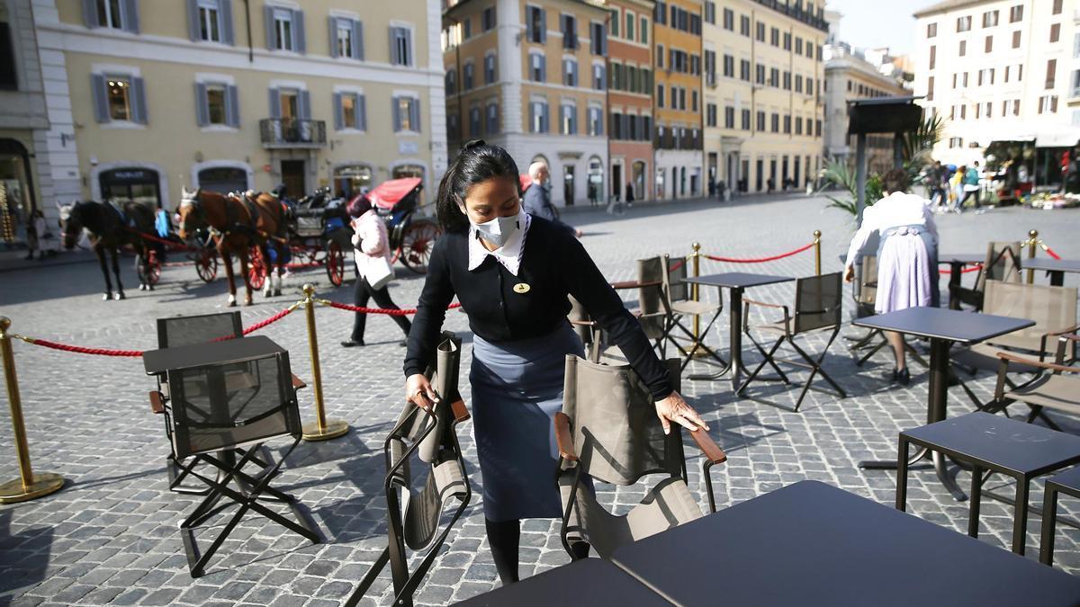 Una camarera prepara una terraza en Roma.