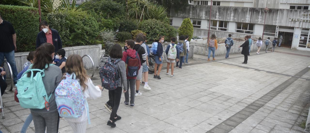 Jóvenes hacen cola ante un instituto.