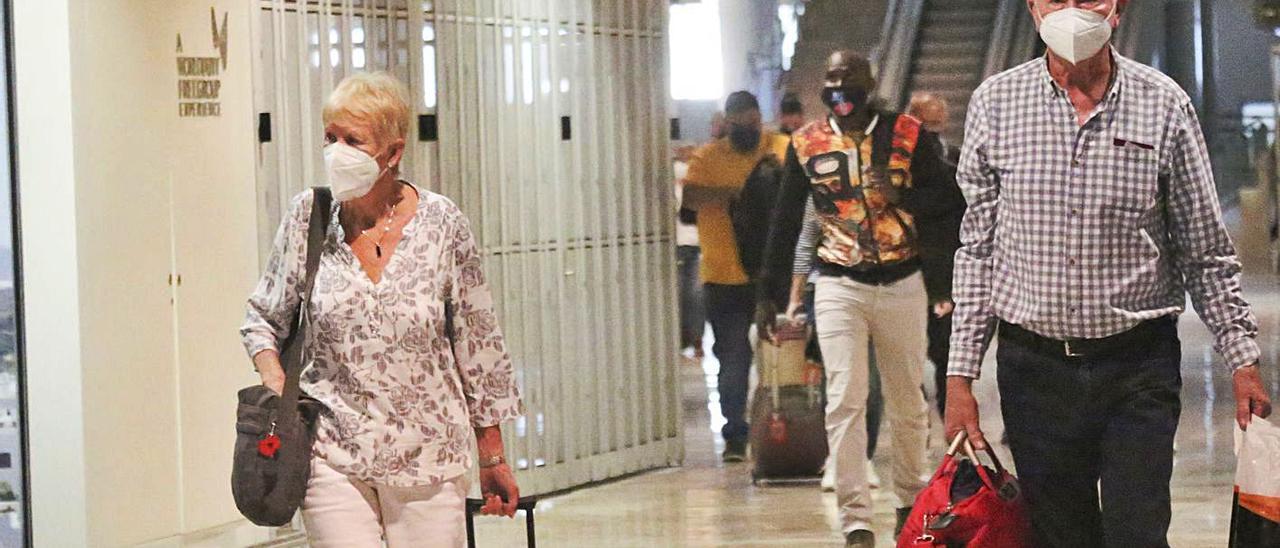 Turistas británicos llegando ayer al aeropuerto. Abajo, pubs británicos en Benidorm. | PILAR CORTÉS/ R.PAGÉS