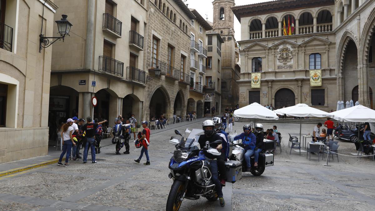 Varios motoristas llegan a una Plaza de España de Alcañiz con menos gente que años atrás.