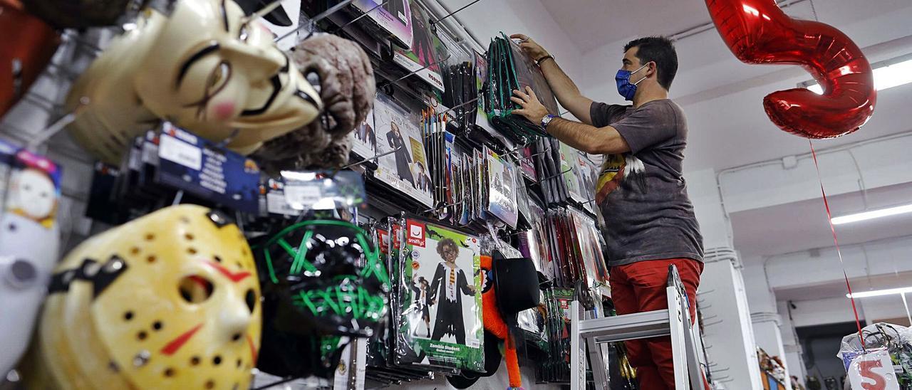 David Ariño, de la tienda Festiplanet, coloca los disfraces de Halloween en las perchas de una de las paredes de su negocio.   | M. A. MONTESINOS