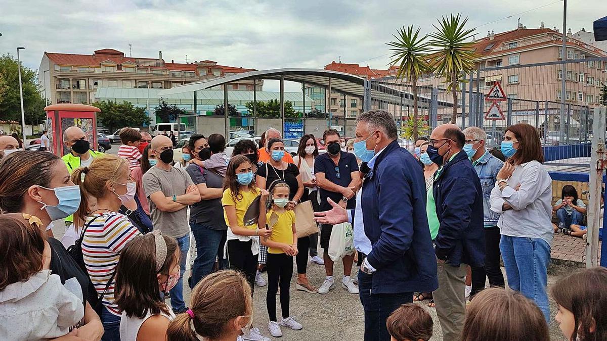 Martín y Pérez Ares conversan con los padres y alumnos concentrados ante el colegio. |   // FDV