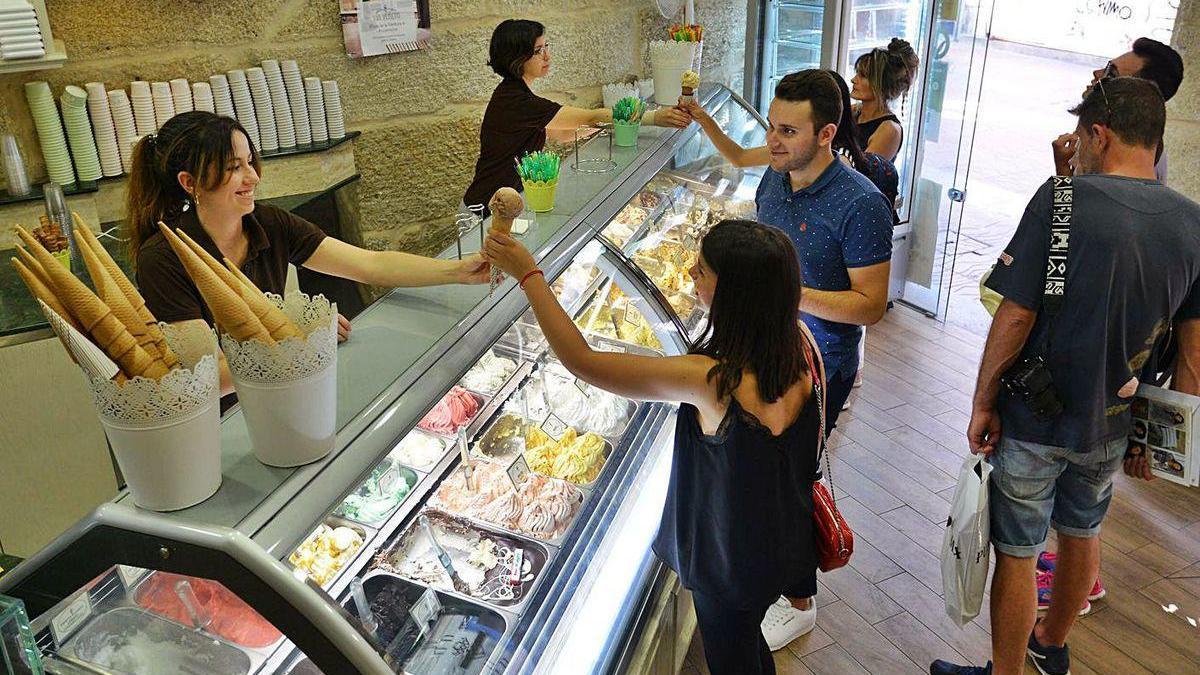 Un grupo de clientes en el interior de una heladería.