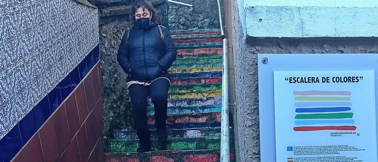 Una mujer desciende por la Escalera de Colores de Ribadesella, con la pintura desgastada.   Eva San Román