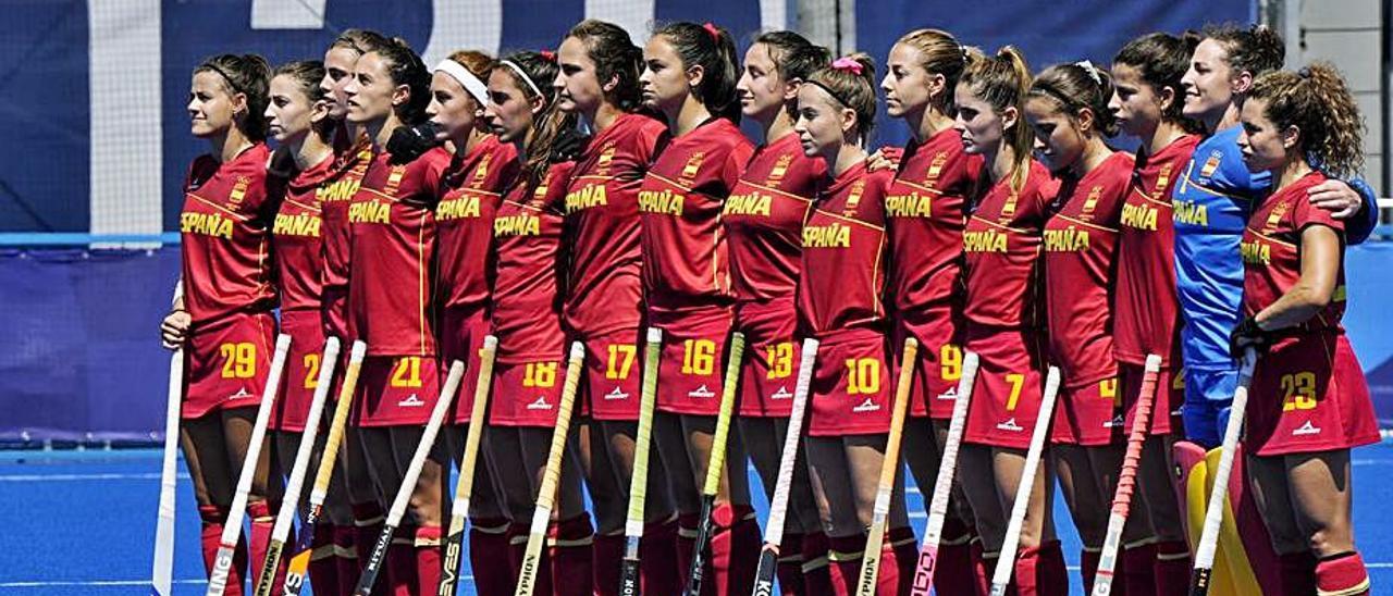 La selección española escuchando el himno antes del comienzo del partido, con María López sexta por la derecha. A la derecha, la jugadora asturiana avanza con la bola. | COE
