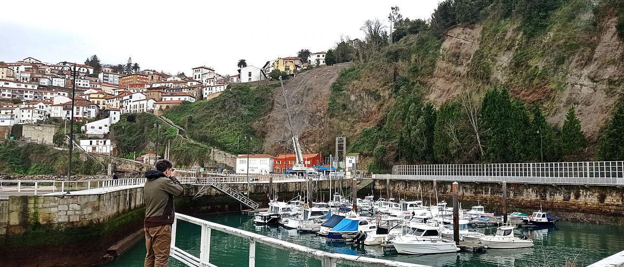 Una grúa trabaja en el talud que argayó sobre la cetárea del puerto pesquero de Lastres. | Eva San Román