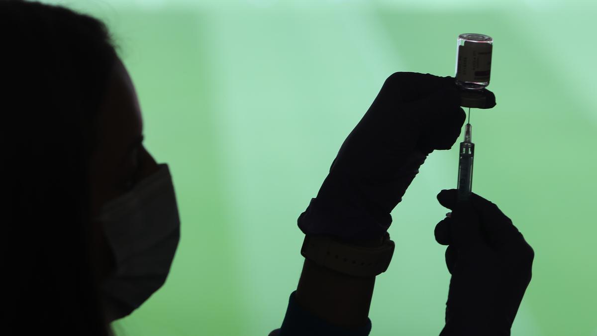 Una profesional sanitaria prepara una vacuna.
