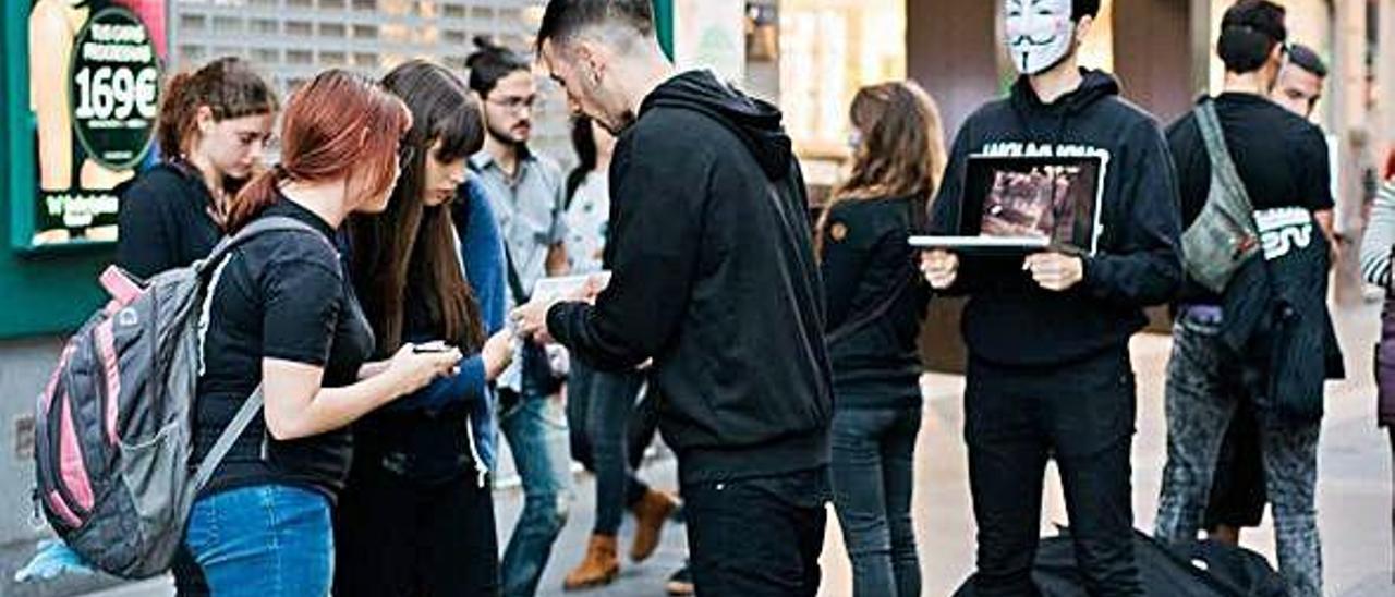 Miembros de 'Anonymous' durante una performance, denominada 'Cubo de la Verdad', en la calle Triana.