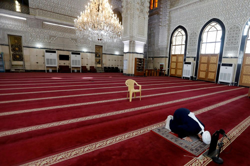 An Iraqi cleric prays in an empty mosque, as ...