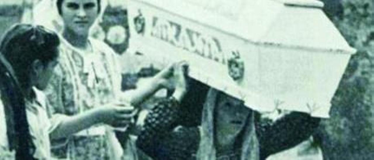 Una mujer porta en procesión un ataúd cerrado, en 1951.
