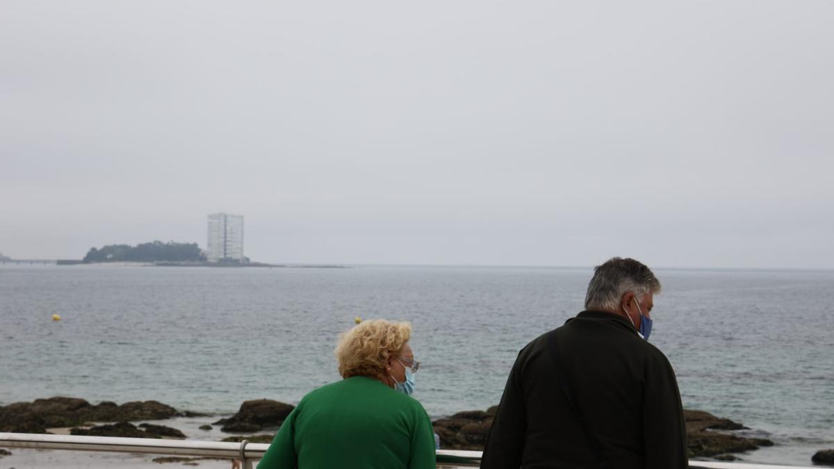 Dos personas en la playa de Samil.