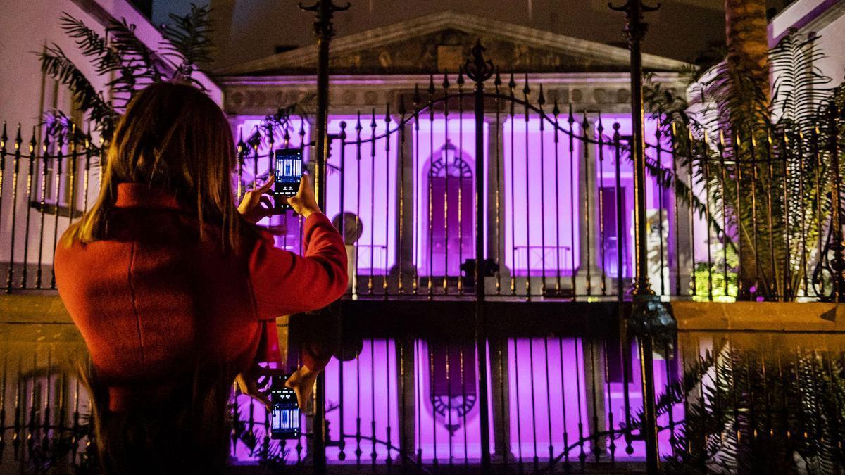 Una mujer tomando una fotografía ayer por la tarde del Parlamento de Canarias iluminado de malva con motivo de la celebración del 8M.