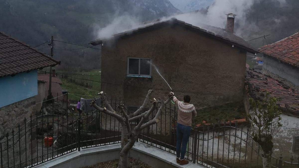 Una vecina, manguera en mano, colabora para sofocar el incendio.