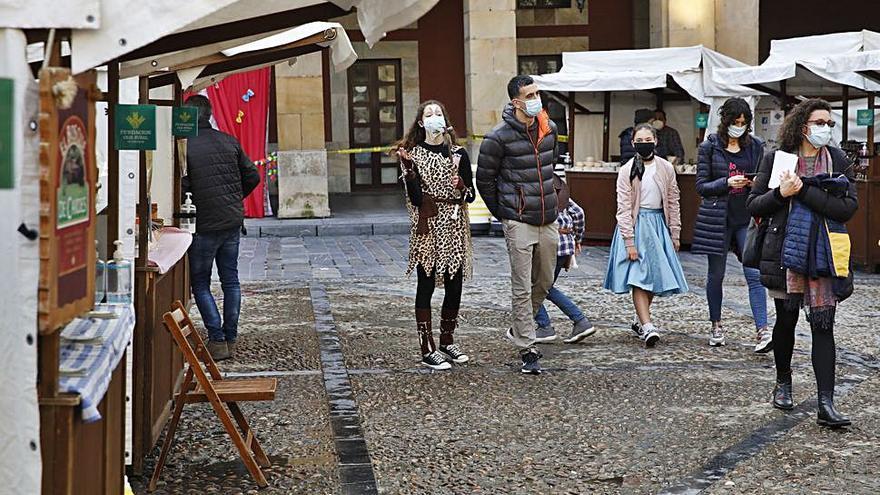 Mercado artesano con disfraces en una plaza Mayor abierta al Antroxu
