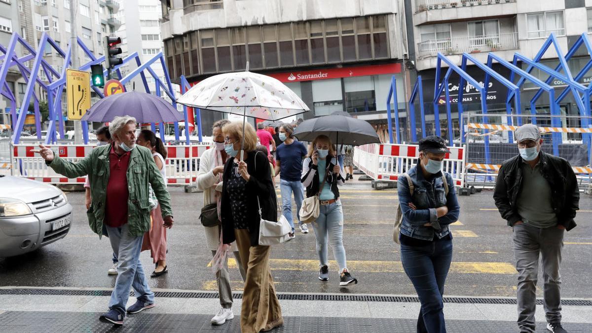 Gente con paraguas bajo la lluvia en Vigo. // José Lores
