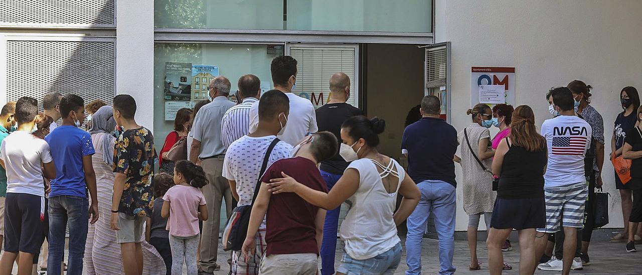 Ciudadanos esperan a las puertas de la Oficina Municipal de Atención al Ciudadano de Carrús, el pasado mes de julio.