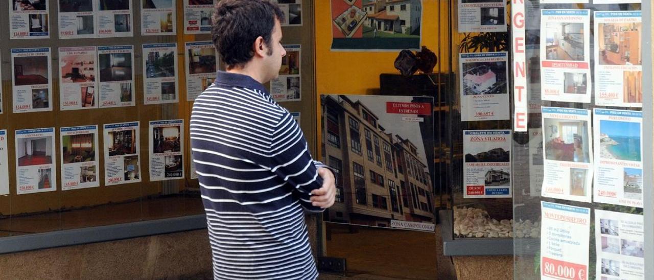 Un joven observa las ofertas de una inmobiliaria. // R. Vázquez