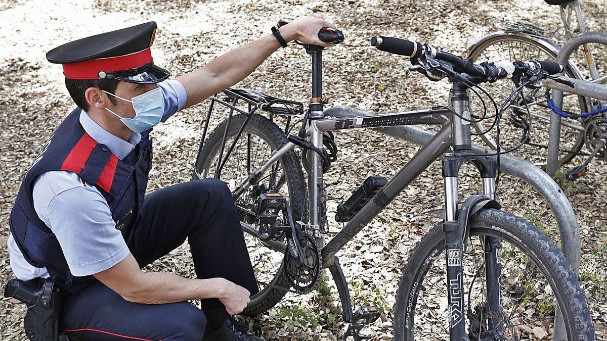 L'agent dels Mossos Sergi Jaén comprovant el número de bastidor d'una bici a Girona.