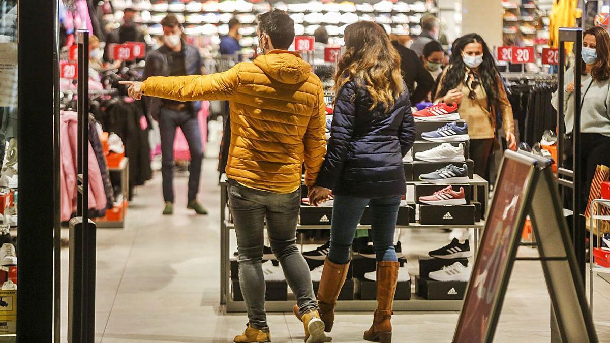 Una pareja entra en una de las tiendas del centro histórico de València. | EDU RIPOLL