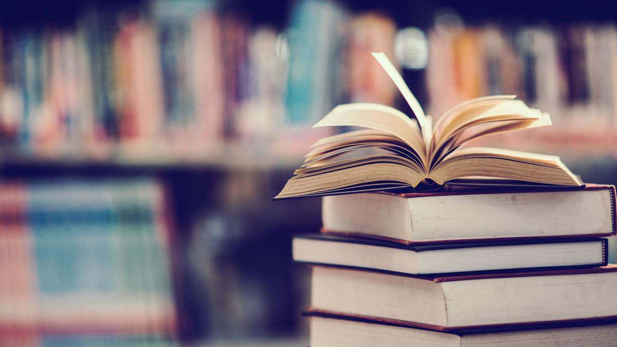 Un libro en una biblioteca con sus páginas abiertas.