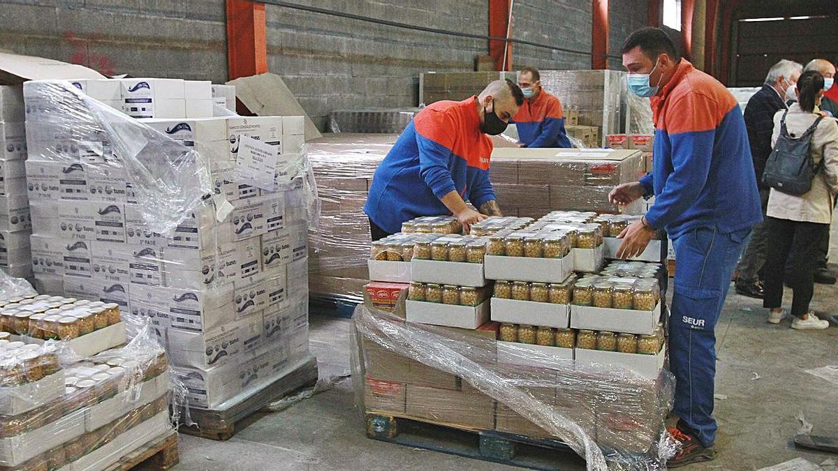 Dos operarios, descargando palés con productos alimenticios. // IÑAKI OSORIO