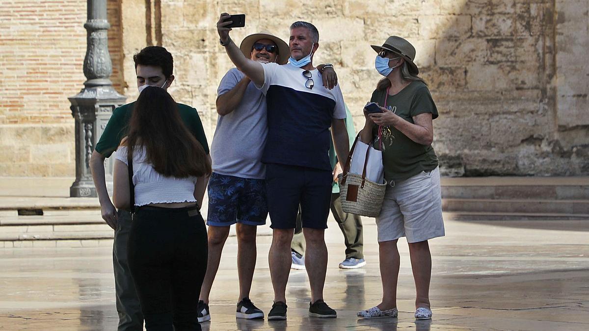 Un grupo de turistas se baja la mascarilla para hacerse una foto con el móvil durante una visita a la plaza de la Virgen, ayer.    M.A.MONTESINOS