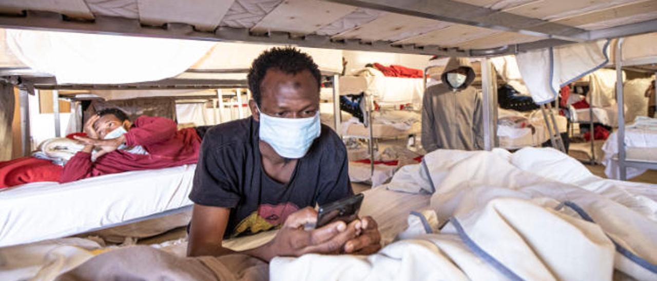 Uno de los inmigrantes africanos consulta su teléfono móvil.