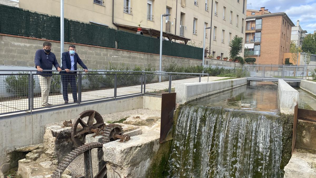L'alcalde de Banyoles, Miquel Noguer, i el regidor d'Urbanisme, Albert Tubert, al costat del salt d'aigua del molí que ara s'ha fet visible